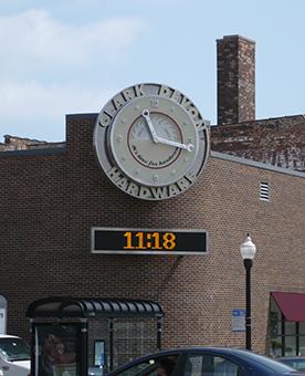 Façade extérieure en briques rouges avec une horloge à cadran et digitale
