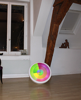 Horloge huchez multi-color posée sur un sol en bois