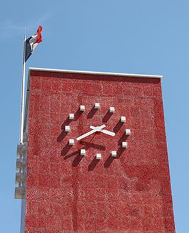 Horloge monumentale sur un mur de briques rouge