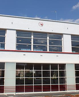 Horloge rouge sur la façade d'un bâtiment blanc
