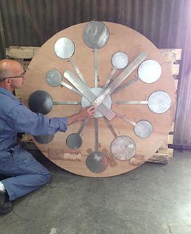 Un ouvrier touchant une aiguille de l'horloge dans un atelier