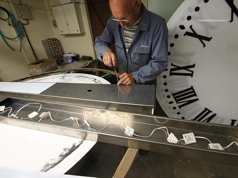 Employé travaillant sur une horloge